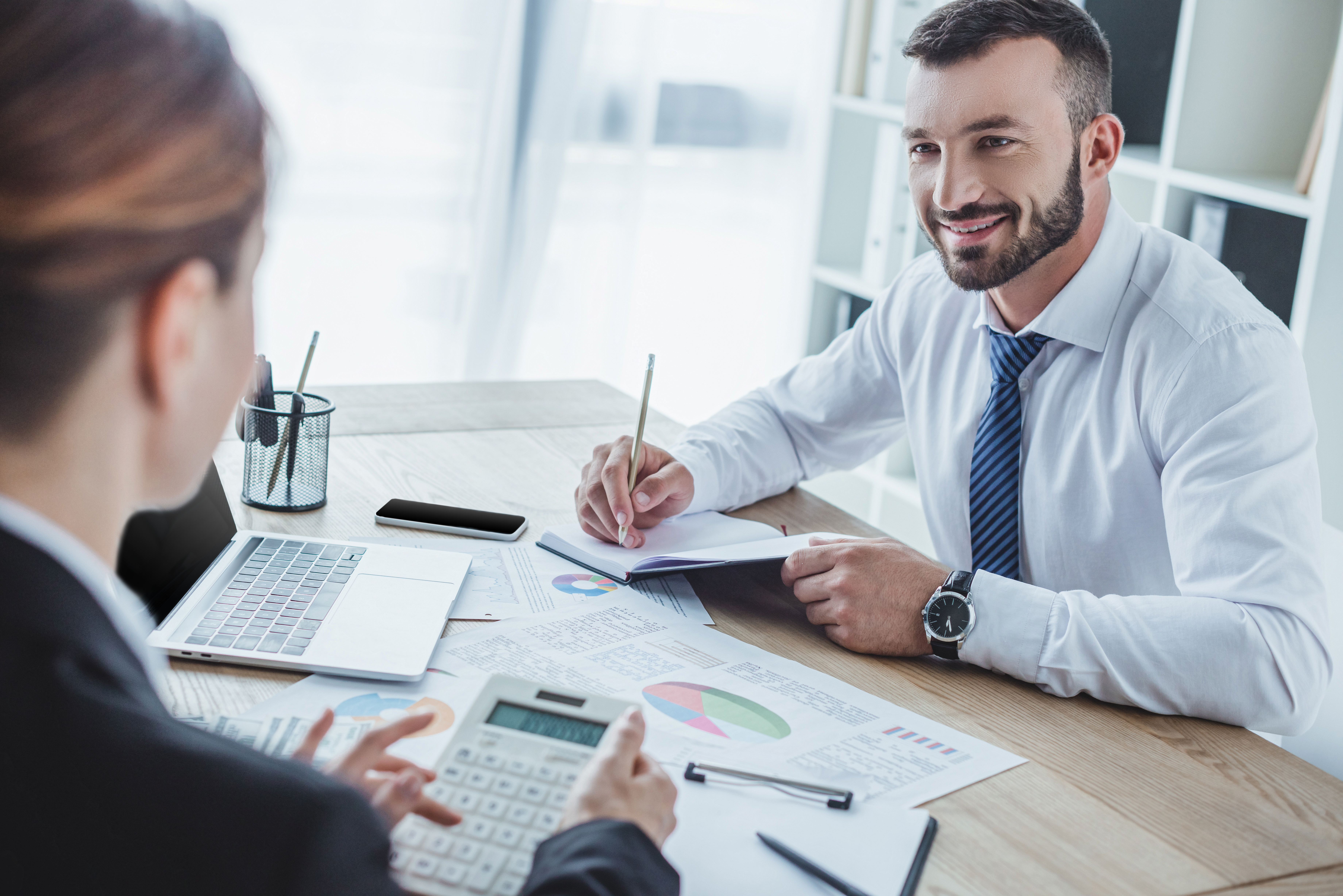 smiling financiers looking at each other during work in office
