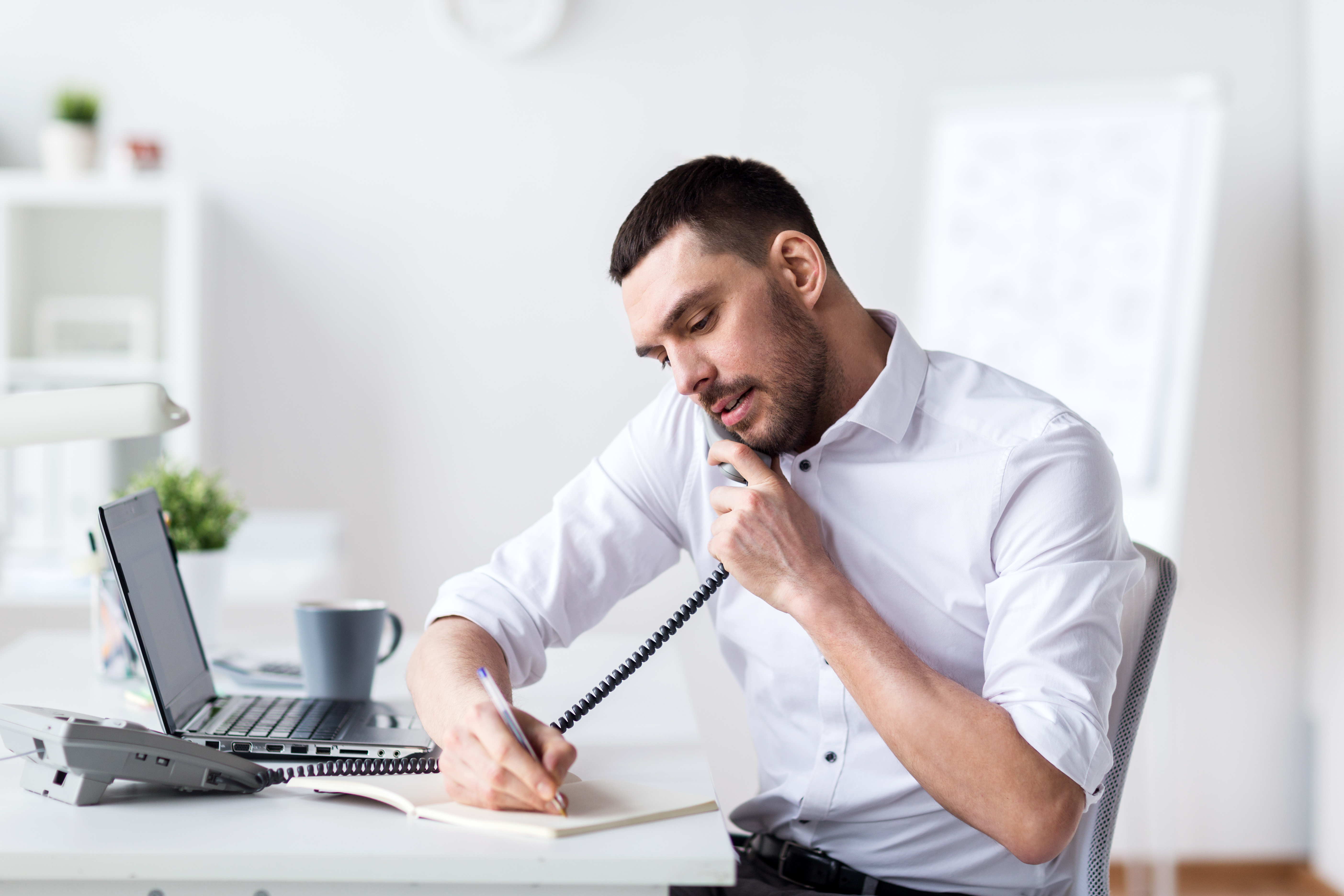 businessman with pad calling on phone at office