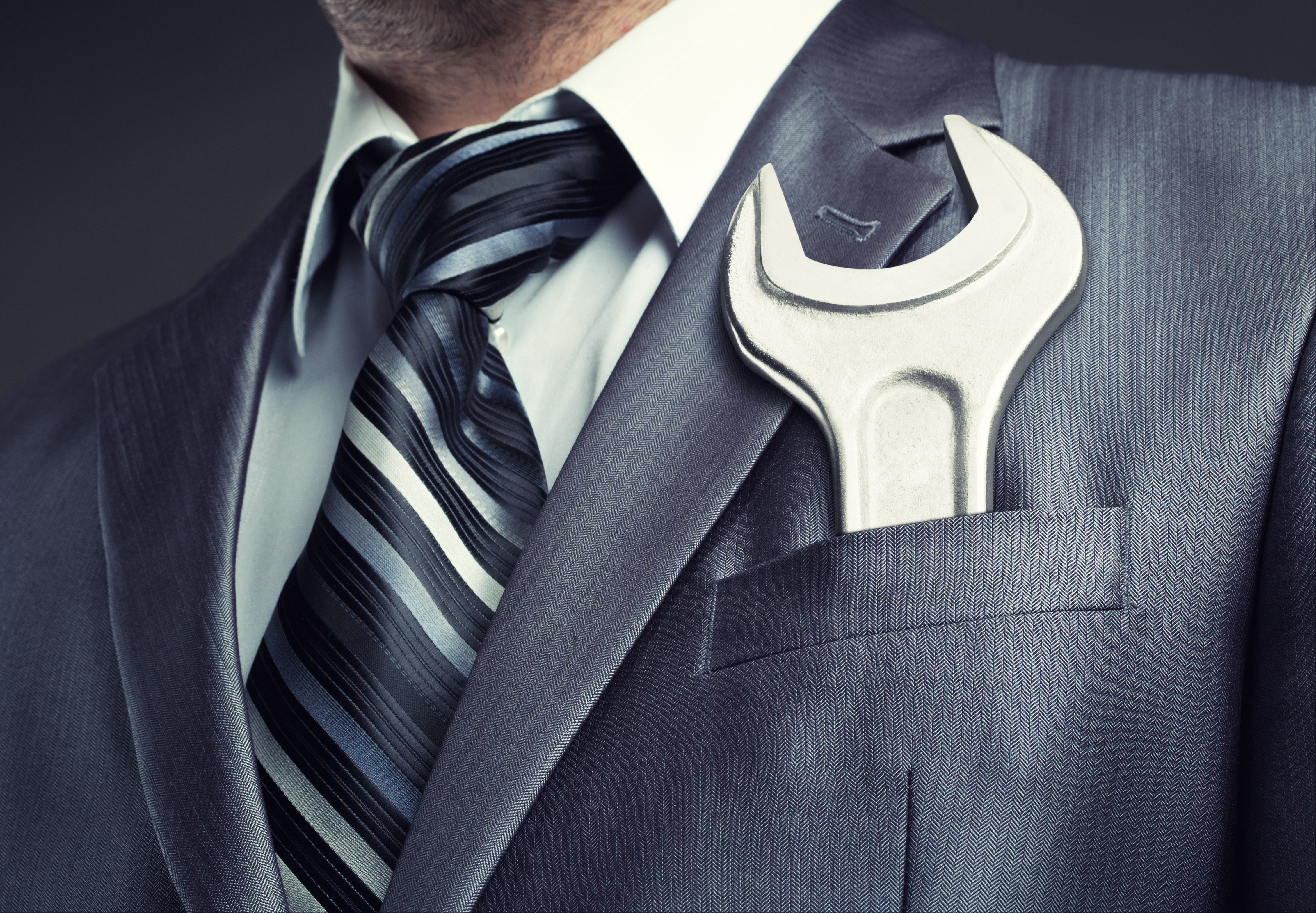 Contractor in a suit with spanner