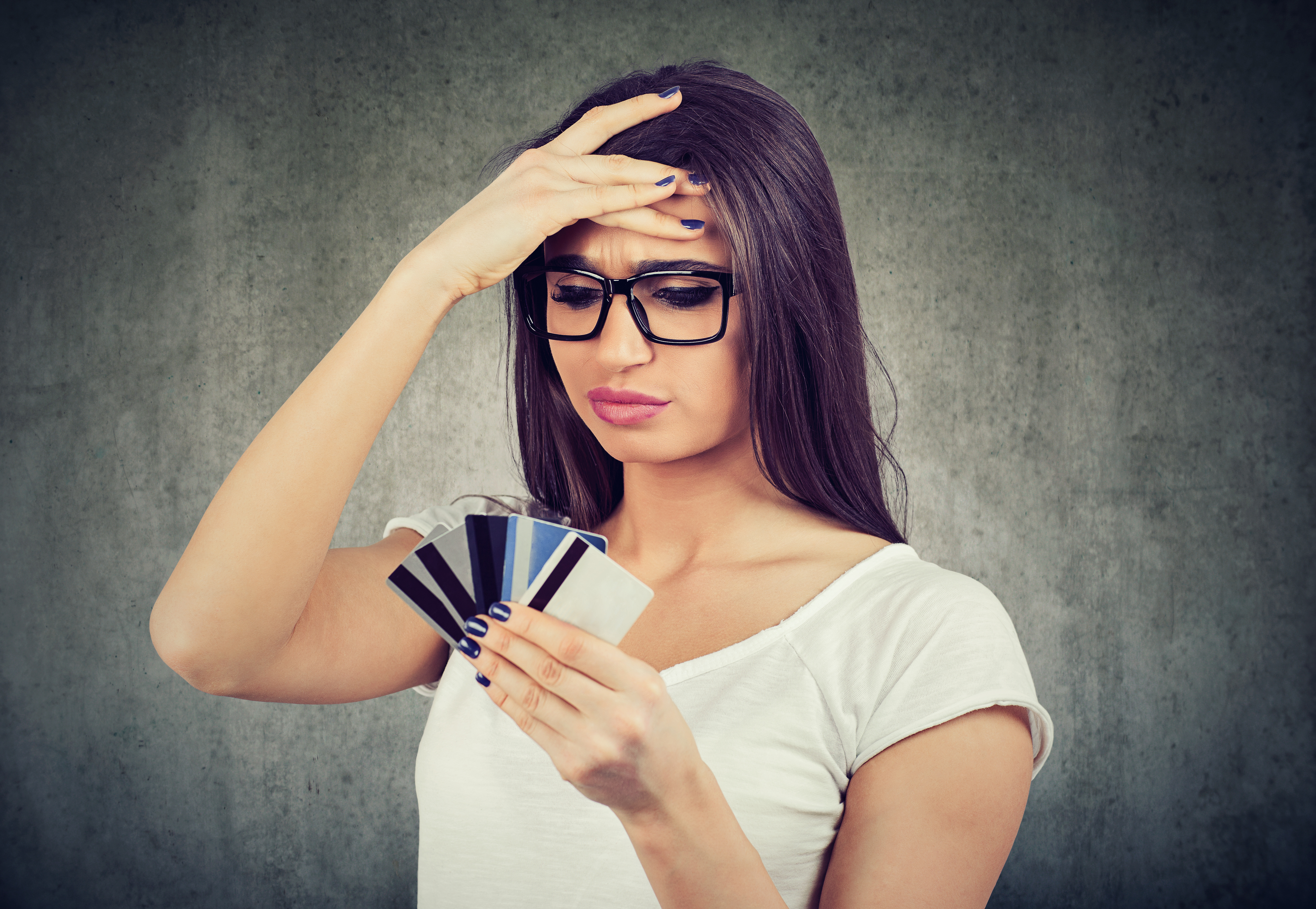 Confused stressed contractor looking at too many credit cards full of debt