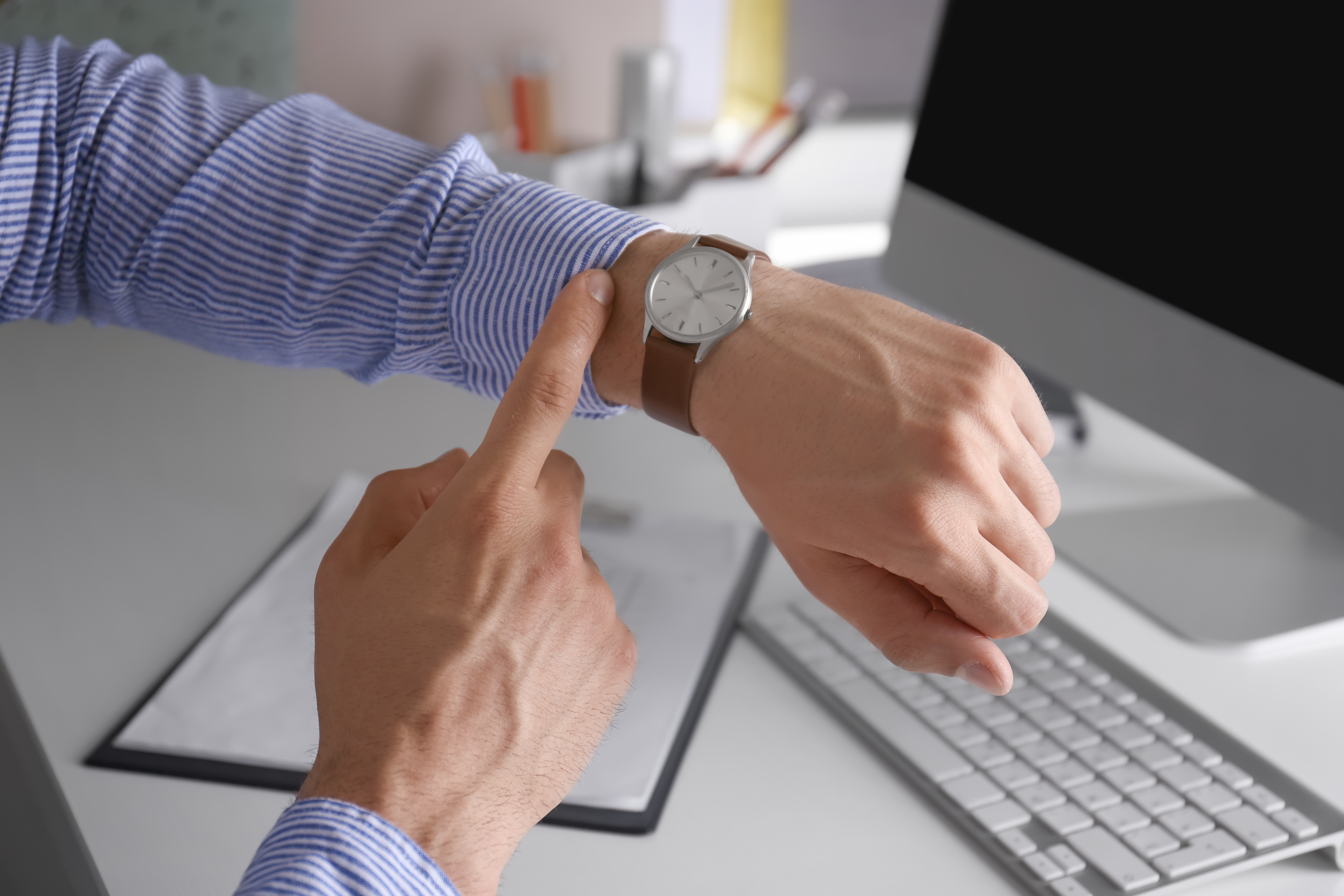 Young man checking time on his wristwatch at workplace