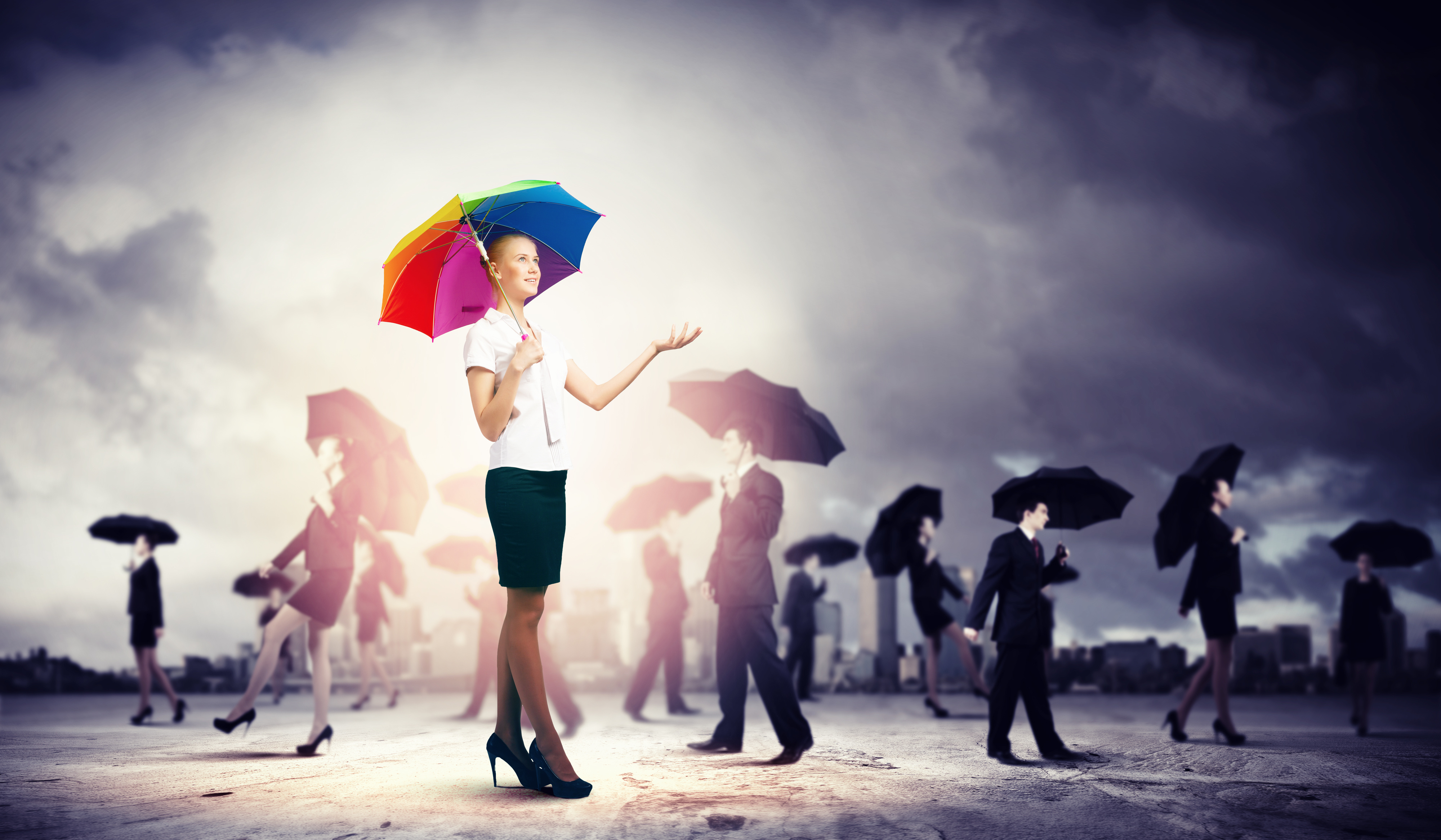 Many people in business attire holding up umbrellas