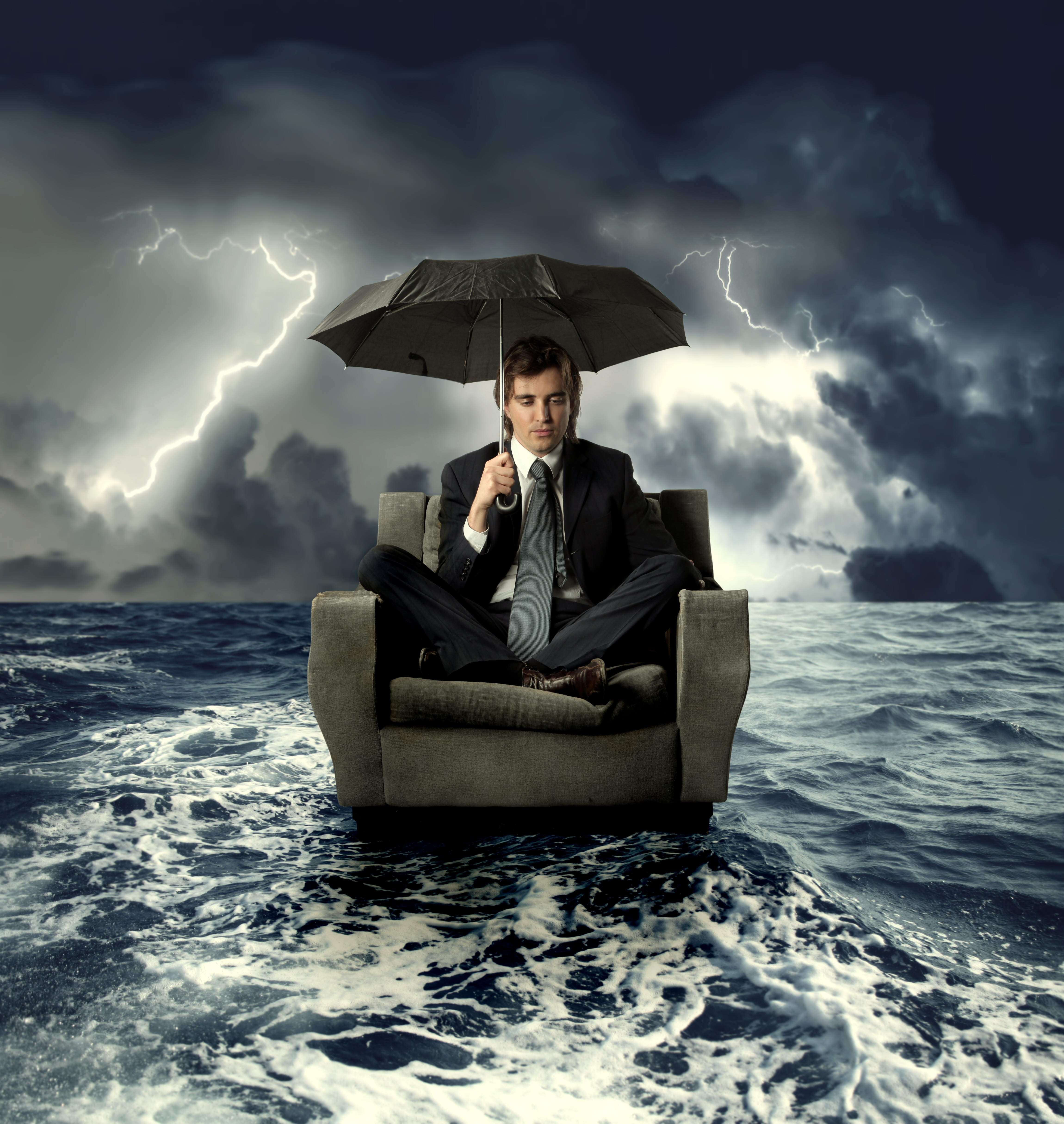 Contractor on a sofa in the sea with umbrella