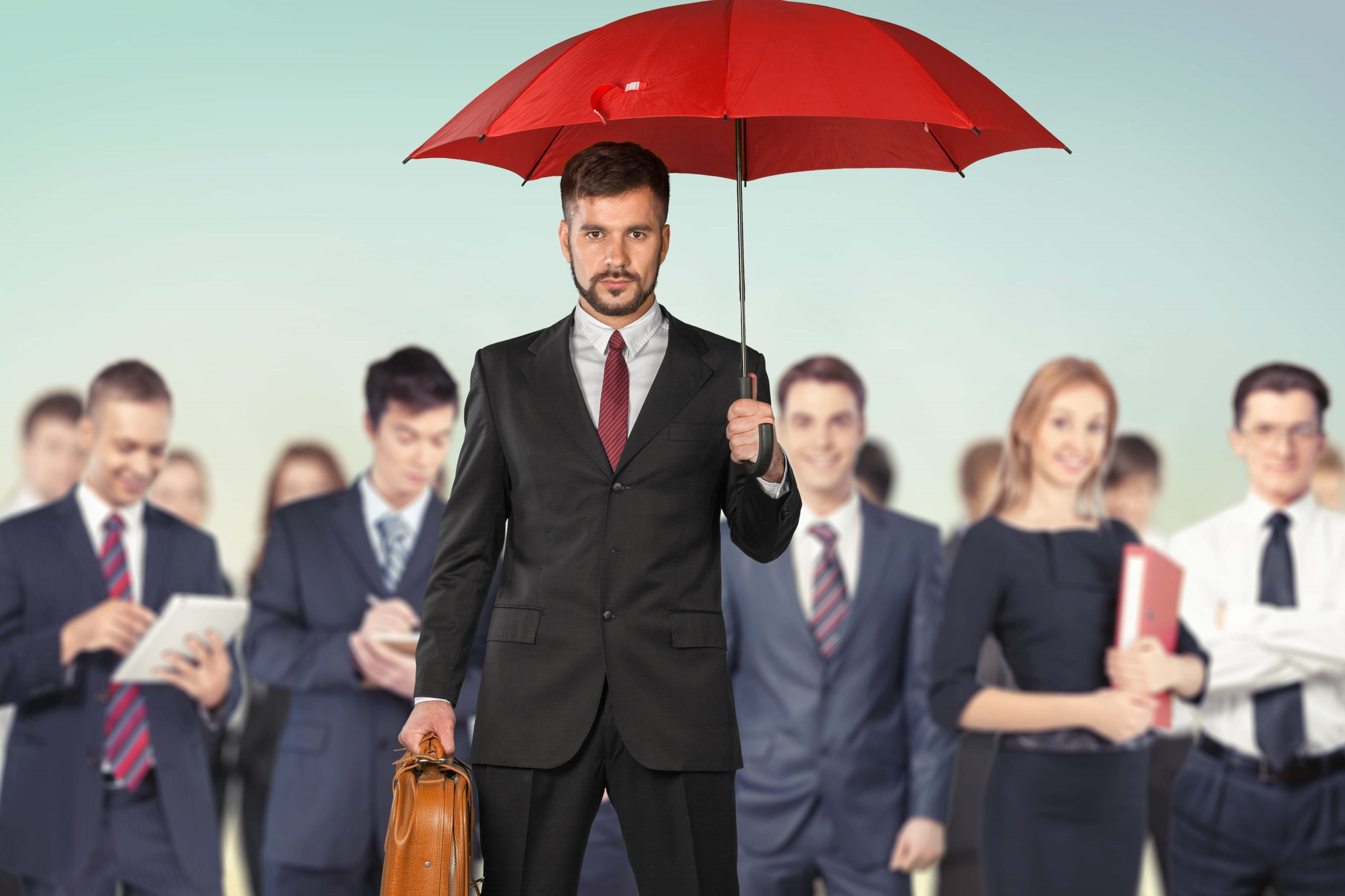 Man holding up the umbrella company with employees in the background