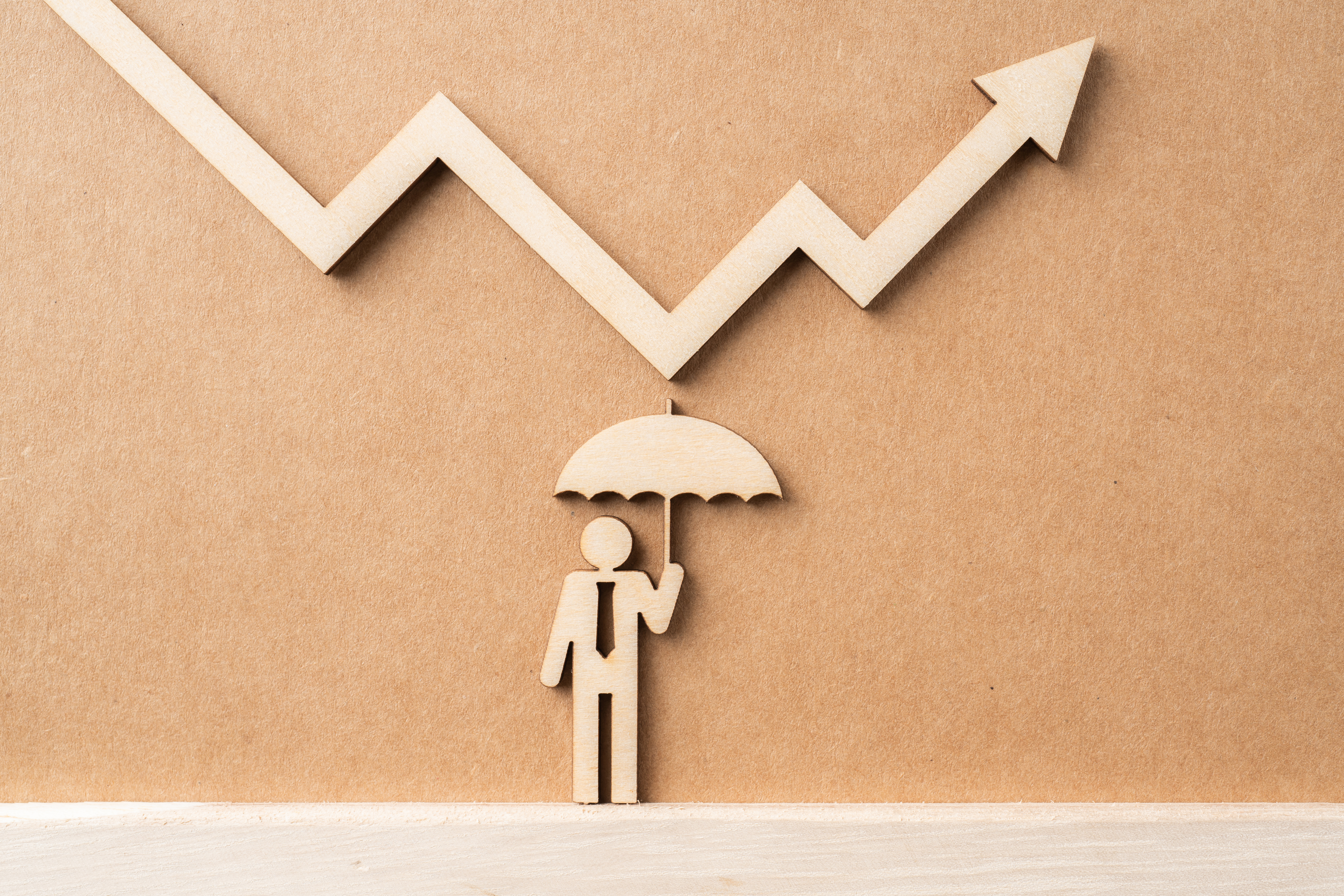 Business and design concept - group of wooden businessman icon with umbrella and arrow on kraft paper. it's stock market financial concept