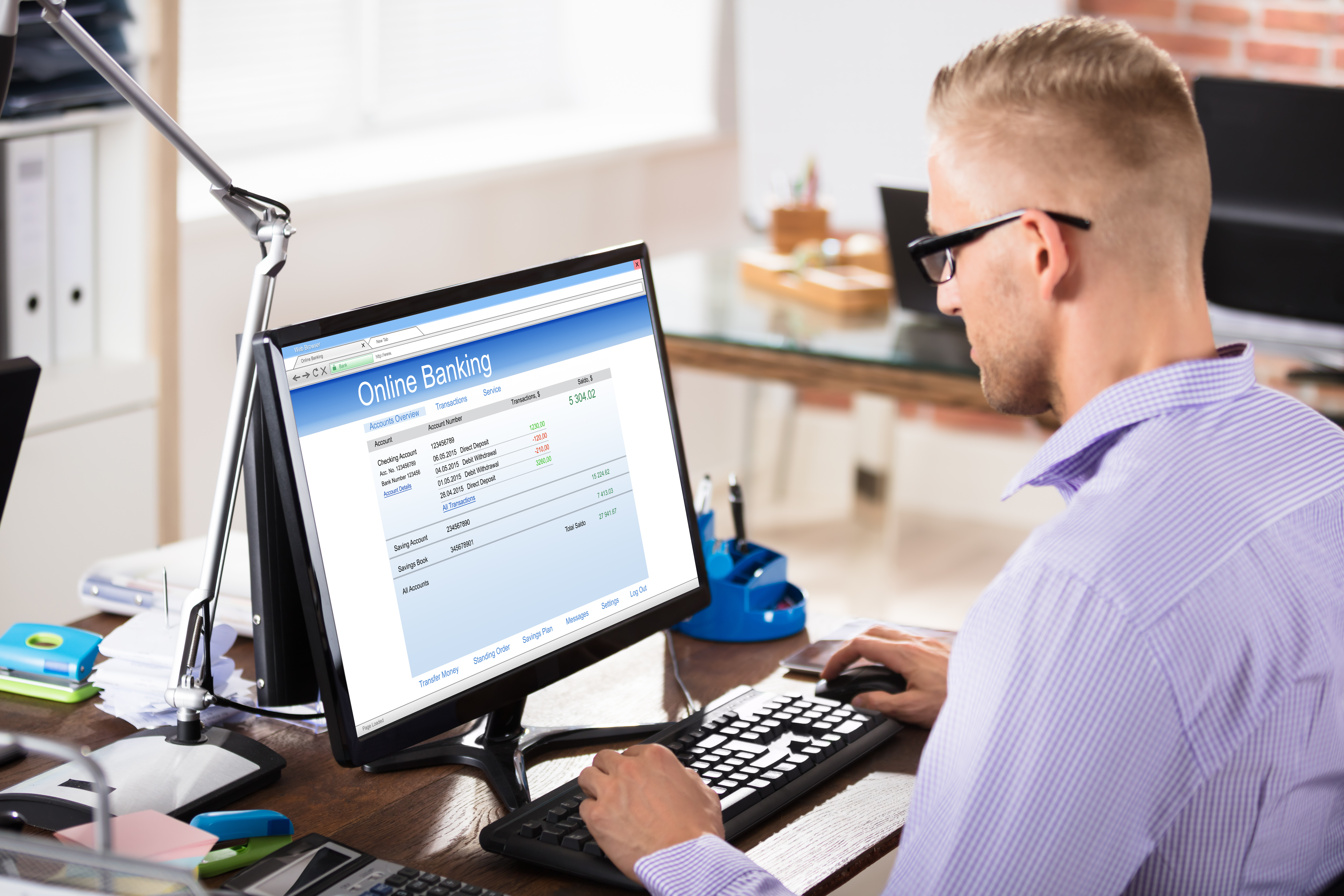 Young Businessman Wearing Spectacles Doing Online Banking On Computer